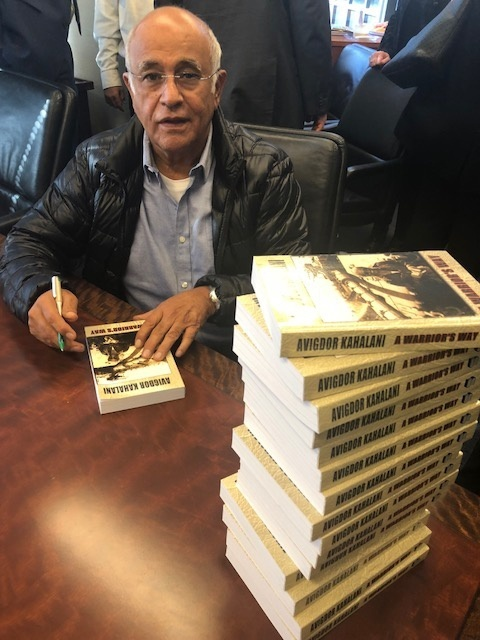Brig. Gen. Kahalani signing complimentary copies of his book.